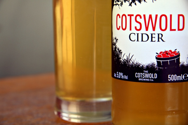 bottle of cotswold cider sitting on the table with a glass next to it