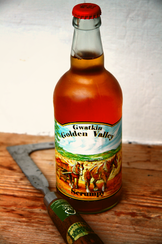 bottle of gwatkin golden valley scrumpy cyder sitting on the table with a weed cutter next to it. very rustic