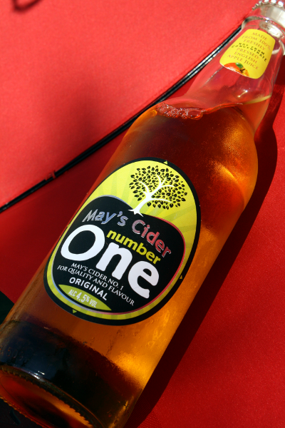 bottle of mays cider number one by the amazing cider company with a red background behind it